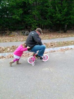 Funny daddy riding on baby's bicycle